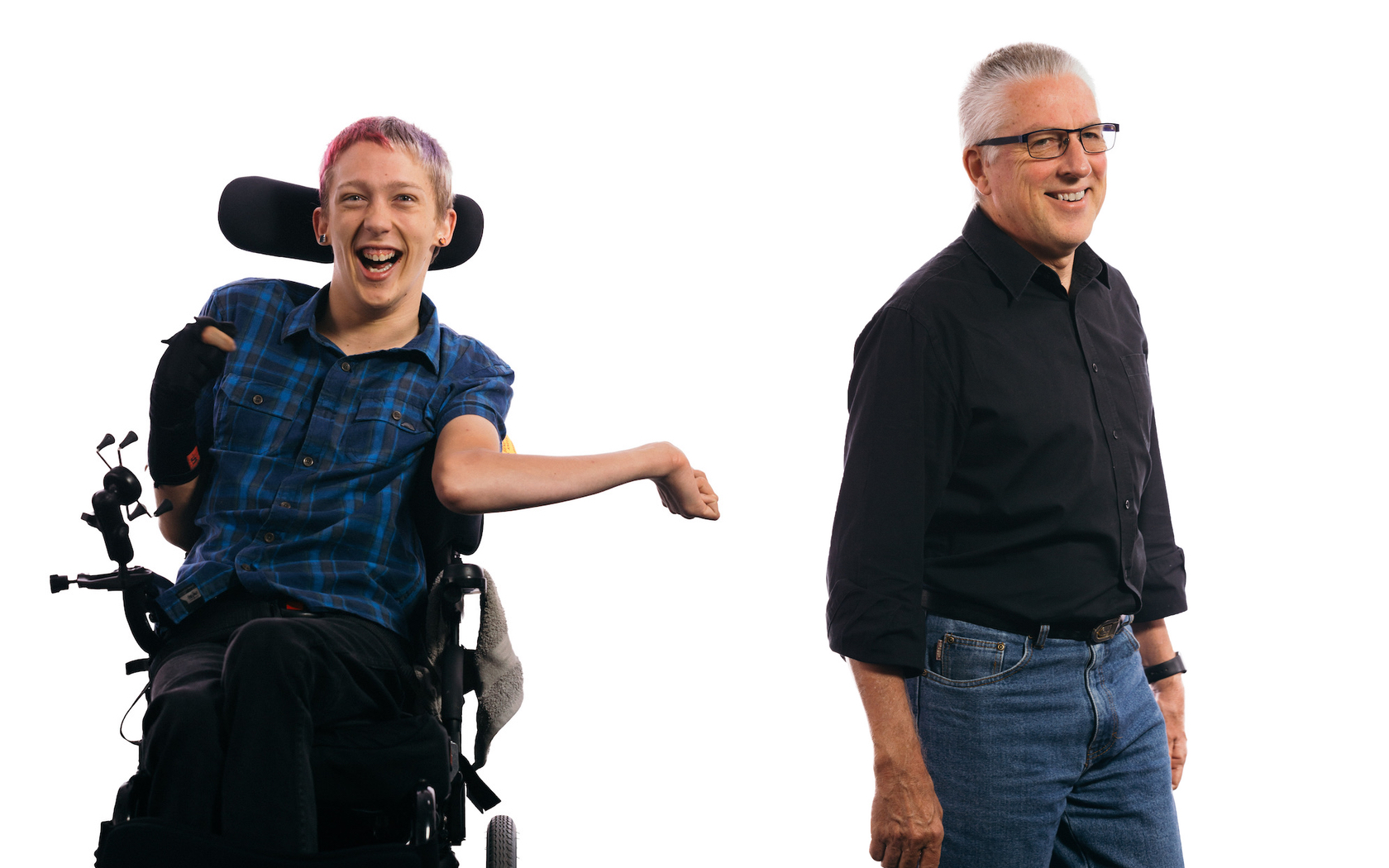 A middle-aged man wearing glasses stands and smiles off-camera. Next to him a young man with faded red and blue hair, seated in a wheelchair, smiles to camera.